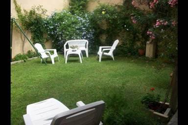 Jardin clos de 50 m2 propre à l'appartement avec coin repas ombragé, barbecue, chaises longue et jeux pour enfants