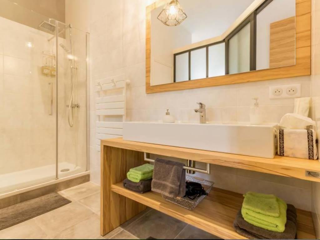 Derrière sa paroi d'atelier se cache une salle de bain une grande vasque, douche et wc séparés.