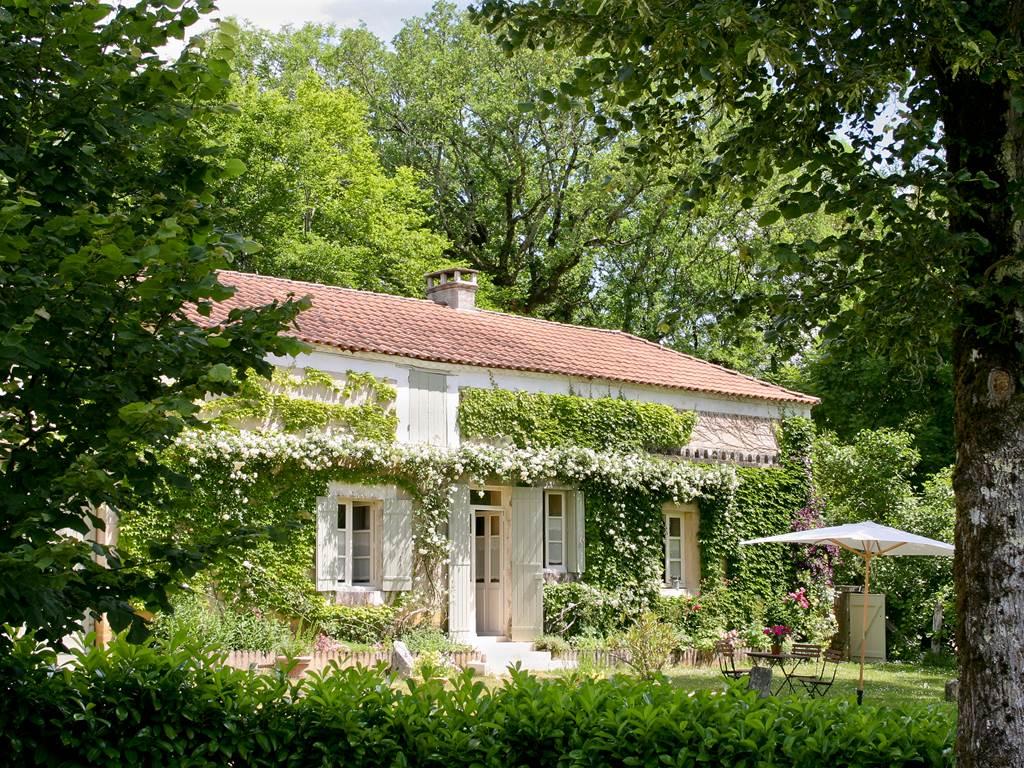 La façade sud de la Maison de Marc à l'ombre des grands arbres et des rosiers blancs