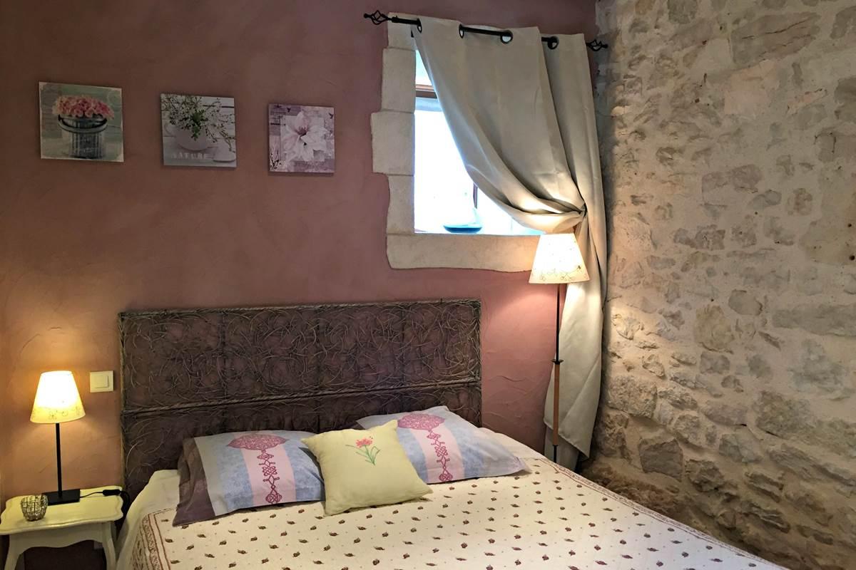 La chambre avec un grand lit, murs en pierres et peints à la chaux, fabrication maison