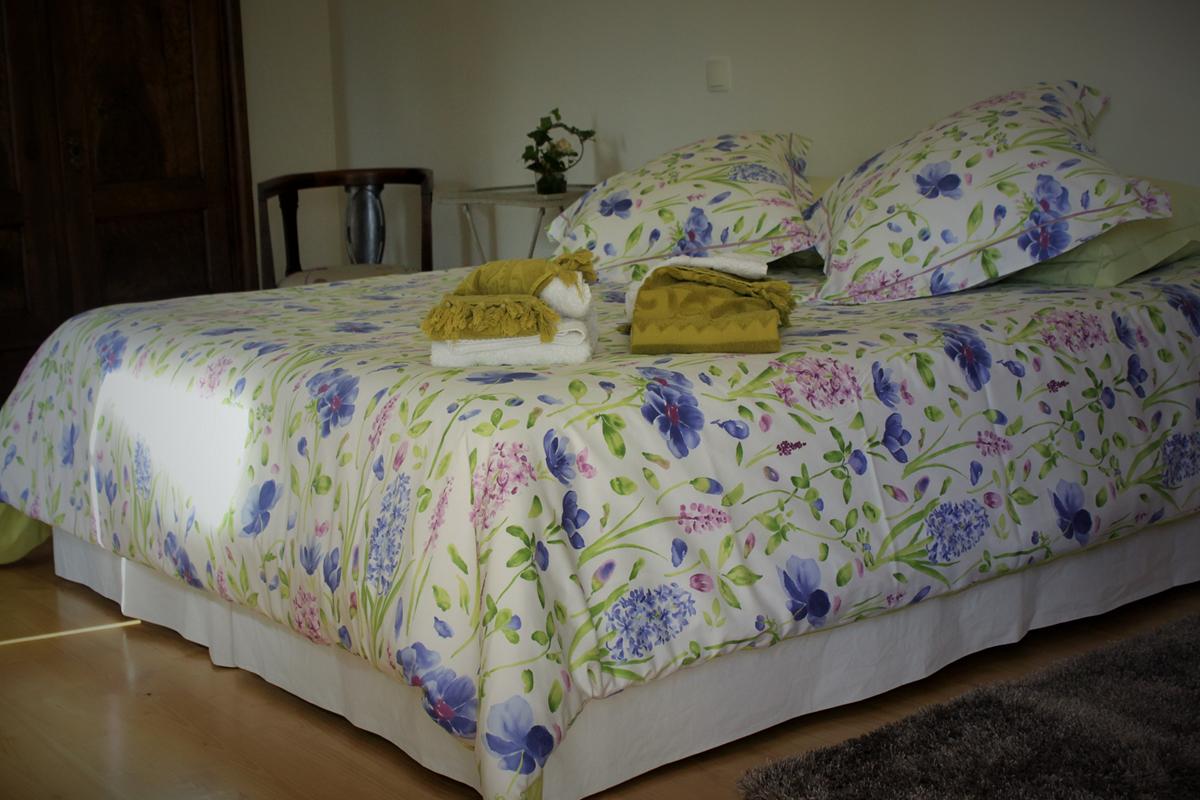chambre Léa, parures de lit soignées et changeantes selon les saisons, espace ouvert sur la salle de bain et offrant une superbe vue sur les falaises rocheuses en surplomb de la vallée du Lot