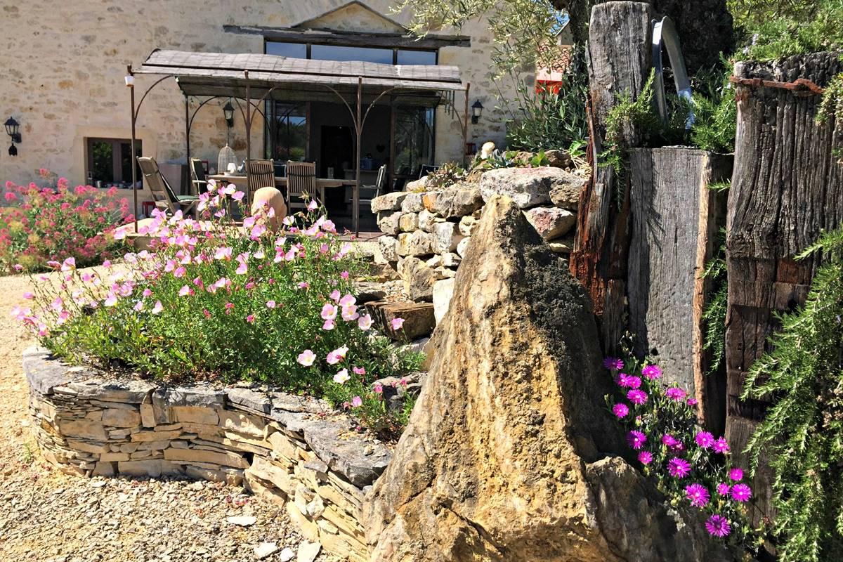 Une structure composée de poutres, de pierres et d'un olivier ticentenaire