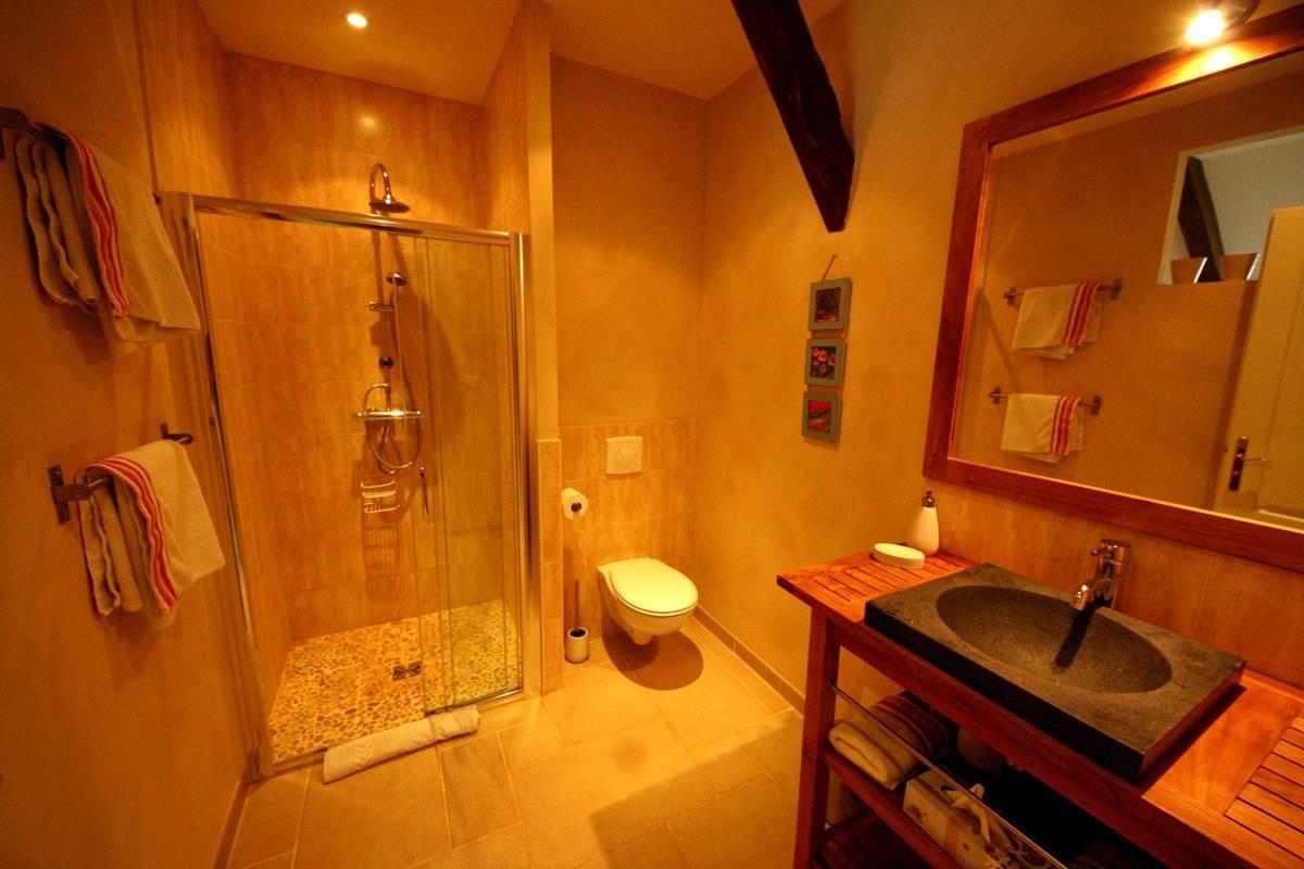La salle d'eau de la chambre Roses de Cahors, douche à l'italienne en galets