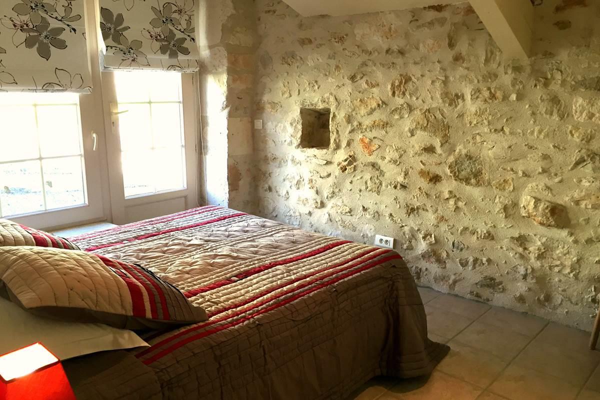 Chambre avec murs en pierre et peints à la chaux