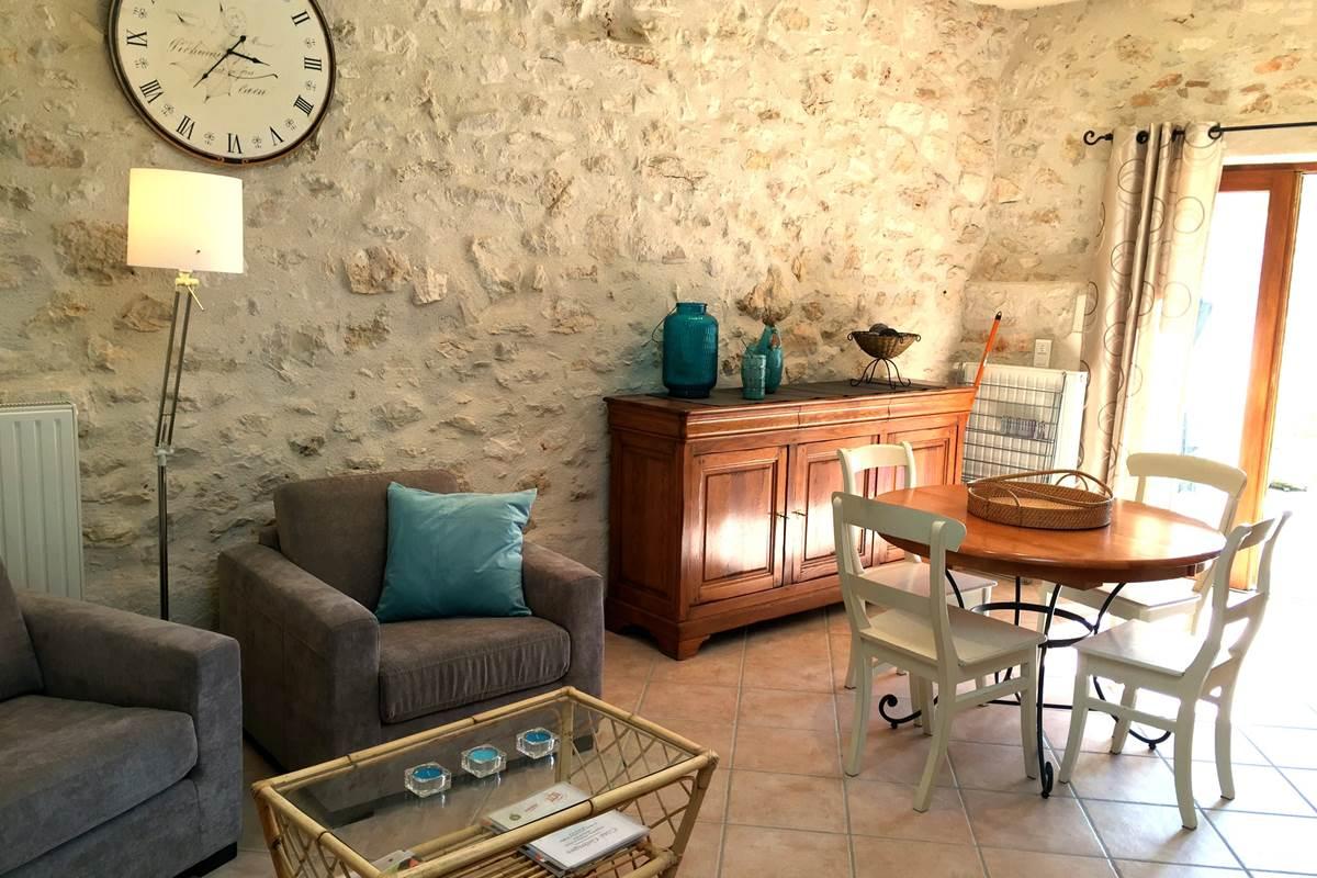 Le séjour avec murs en pierre et murs à la chaux