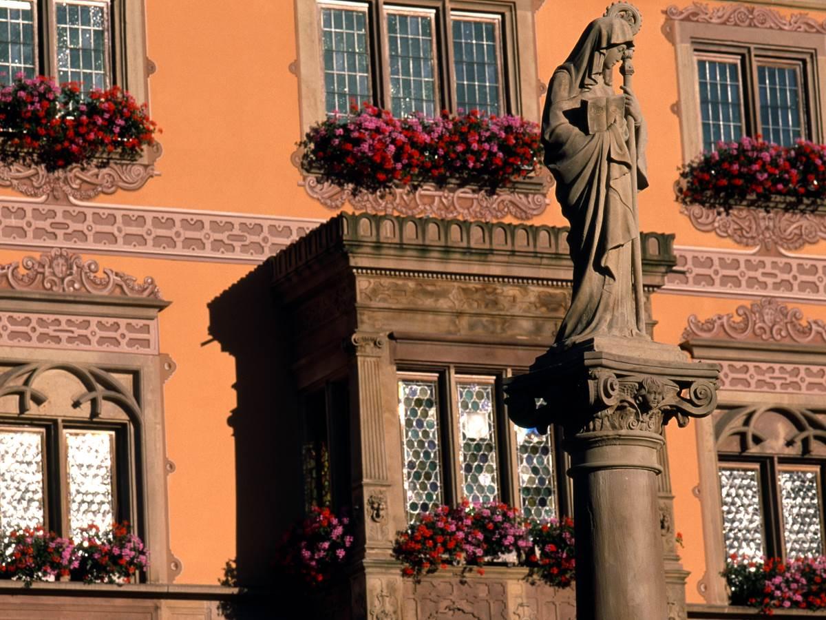 Détail de la façade à colombages de l'hôtel de ville avec la fontaine Sainte-Odile en premier plan.
