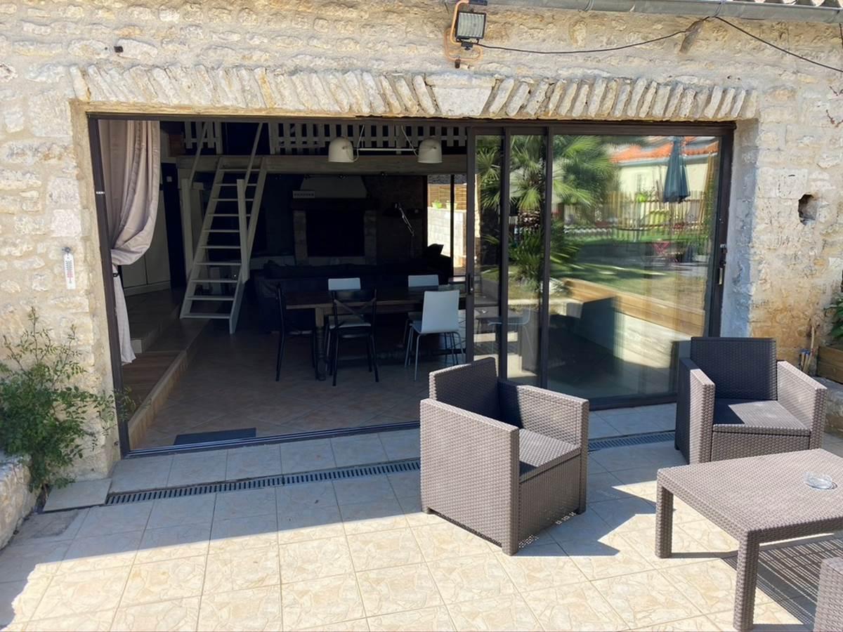 Salon extérieur avec grande baie vitrée donnant dans l'espace séjour