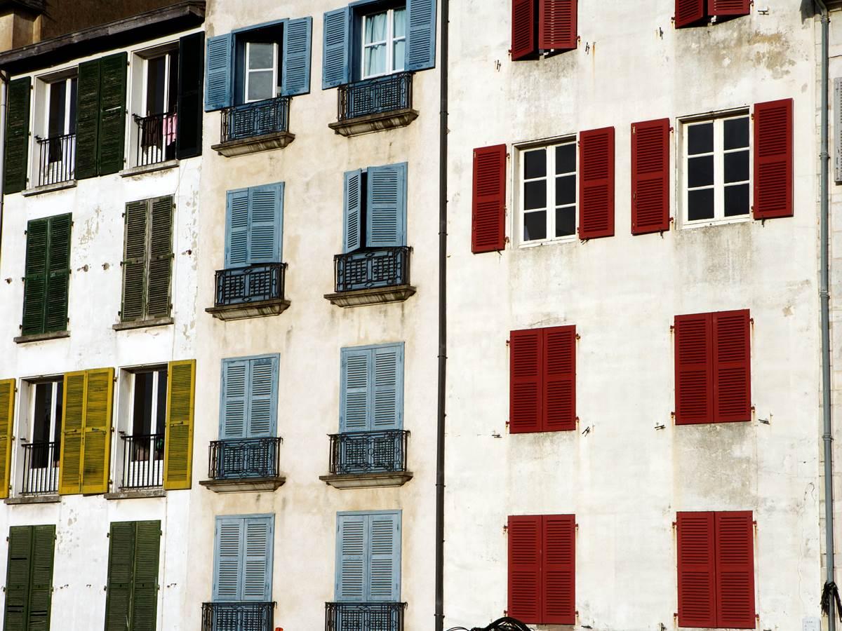 Murs blancs et volets à persiennes peints en rouge, marron, vert ou bleu caractéristiques de Bayonne