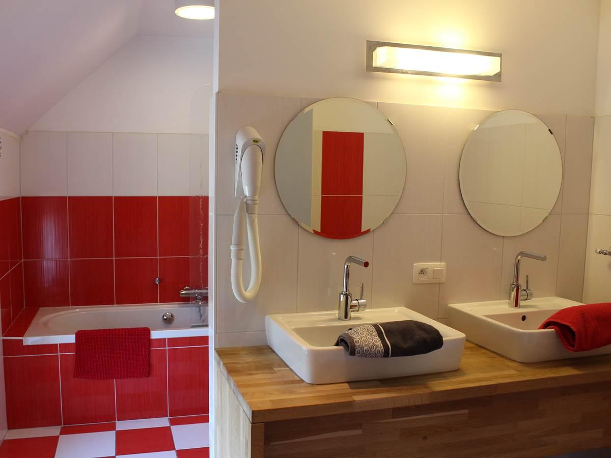 Une grande salle de bain - baignoire  douche - double lavabo - wc  attenant à la chambre rouge