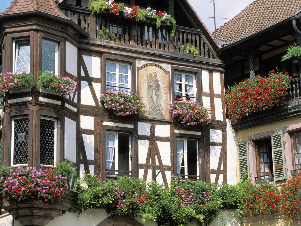 Très belle maison à colombages avec ses rebords de fenêtres fleuris