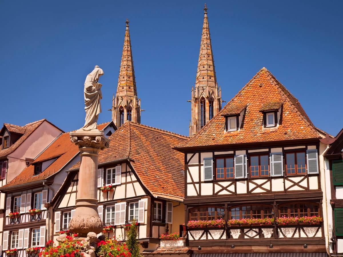Maisons traditionnelles alsaciennes avec la statue de la Vierge Marie au Premier plan.