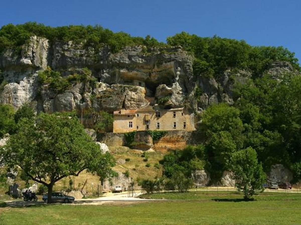 La maison forte de Reignac surgissant du roc et surplombant la Vézère.