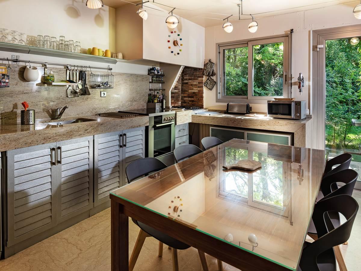 Cuisine donnant sur les deux salles à manger intérieure et extérieure