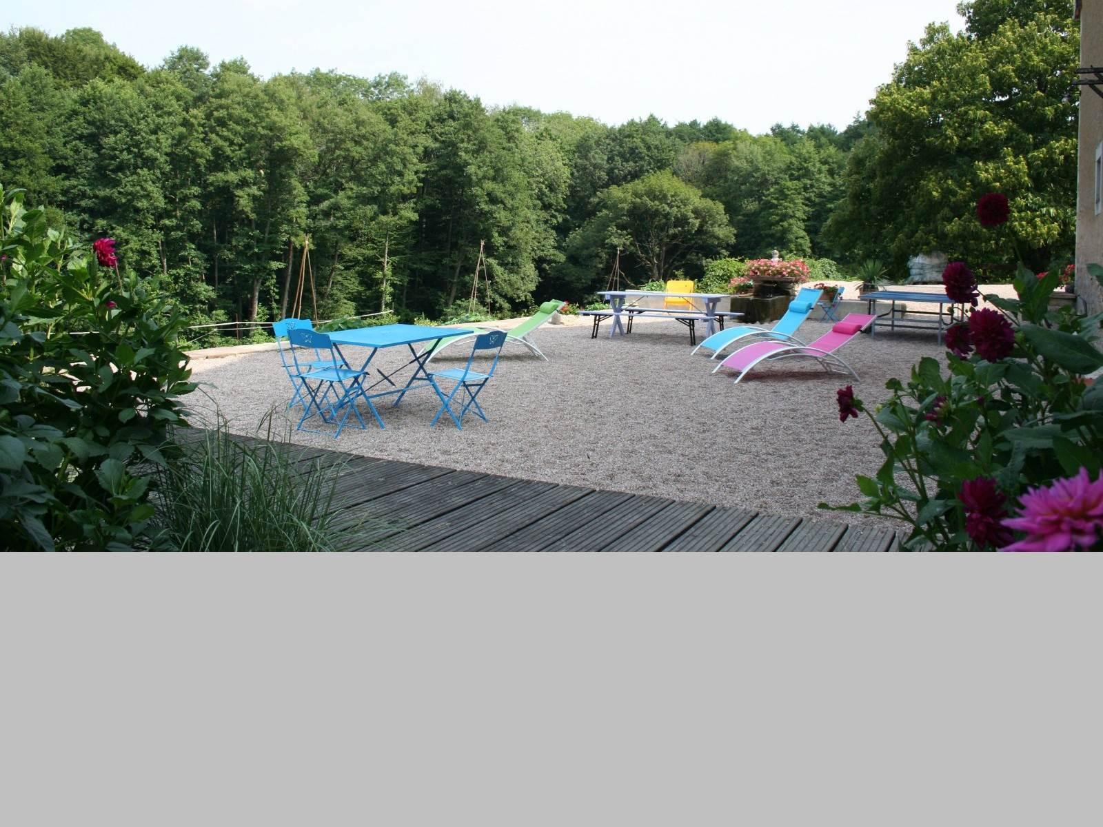 La terrasse avec salon de jardin, chaise longues, fontaine