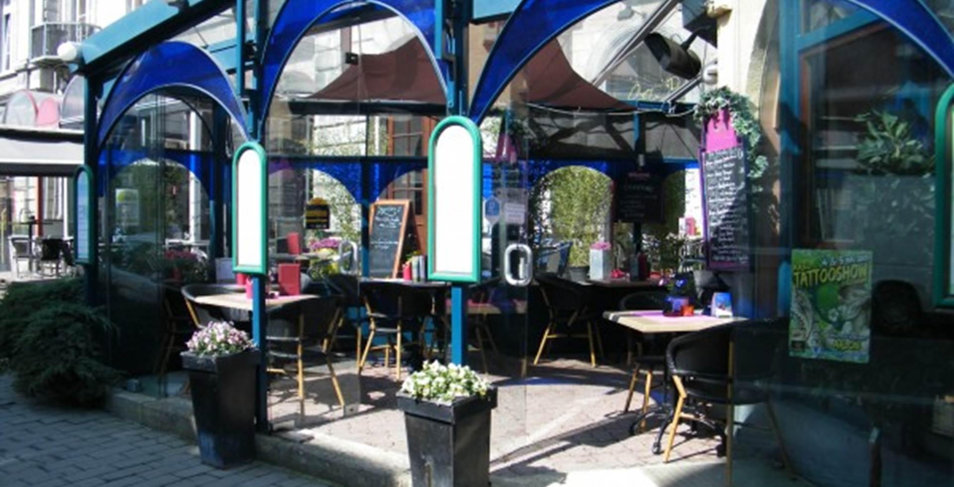 Vue sur la véranda en façade de l'hôtel Les Arcades