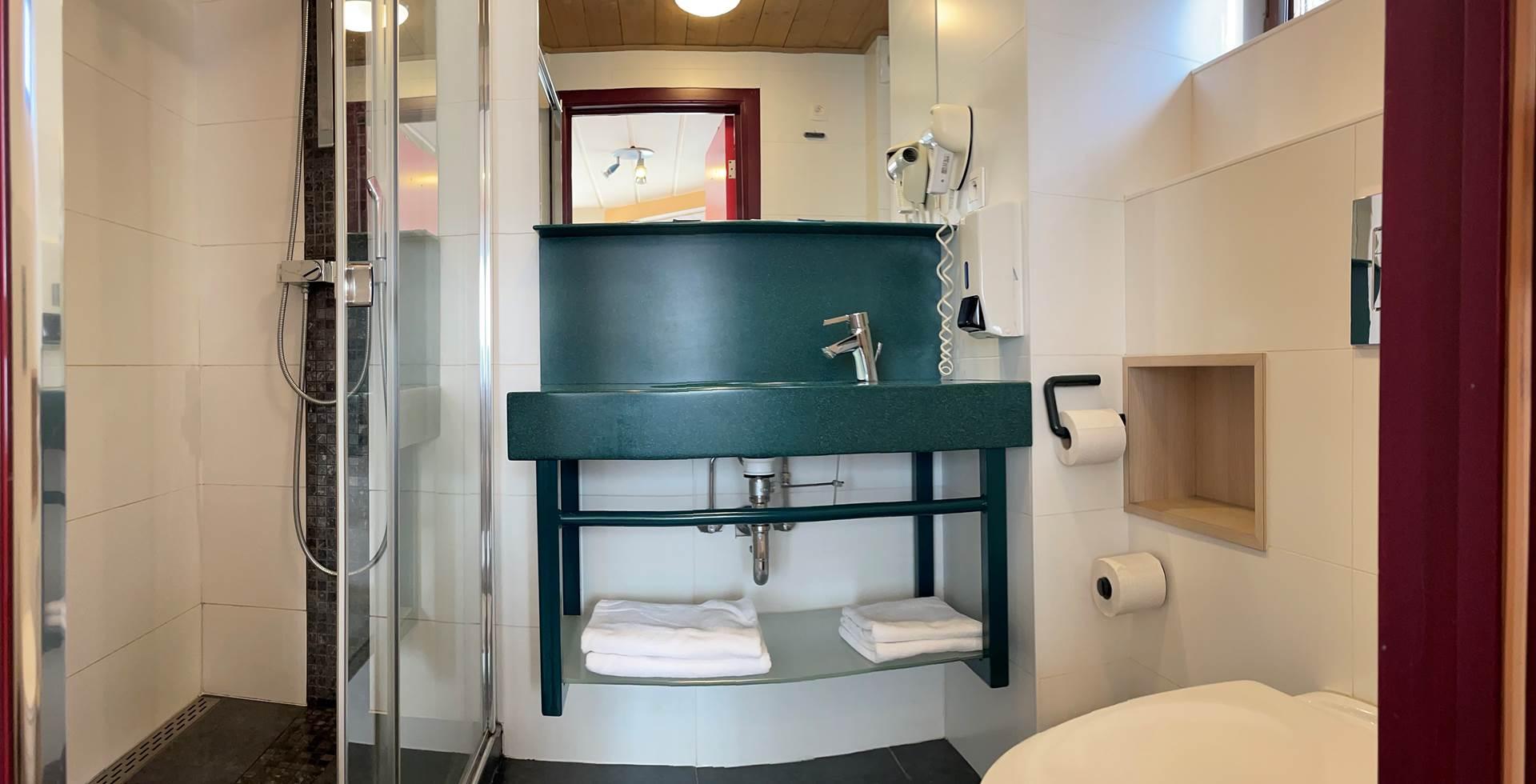Salle de bain privative des Chambres 11 - 21 comprenant une belle douche Italienne, un lavabo, un sèche cheveux et toilettes