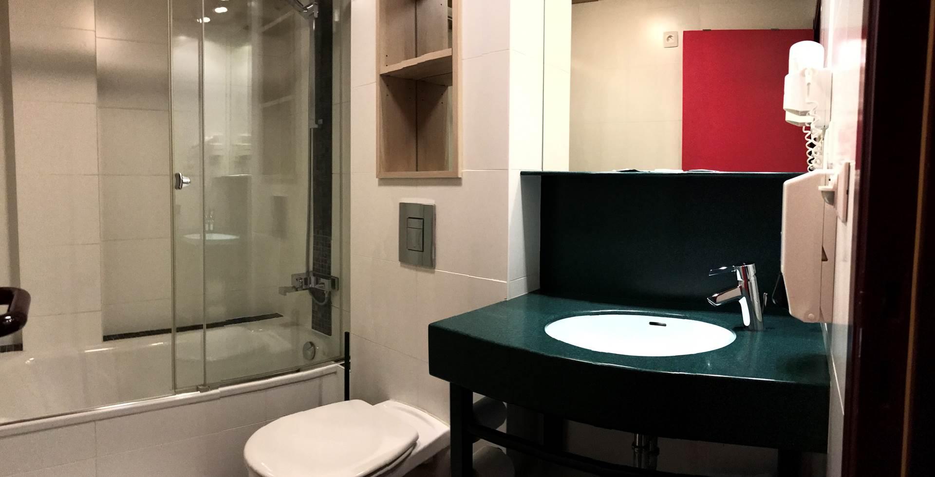 Salle de bain privative de la chambre Twin 13 comprenant une belle douche, un lavabo, un sèche cheveux et toilettes