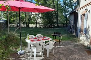 Terrasse avec table, parasol et barbecue