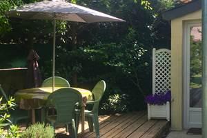 Terrasse privée en bois face au jardin et entrée du gite sur la droite