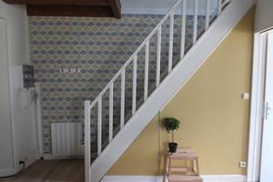 Escalier vers l'étage, entrée vers la gauche et salle d'eau et WC vers la droite