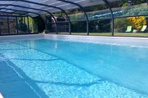 Grande piscine couverte avec espace remise en forme, salon de jardin