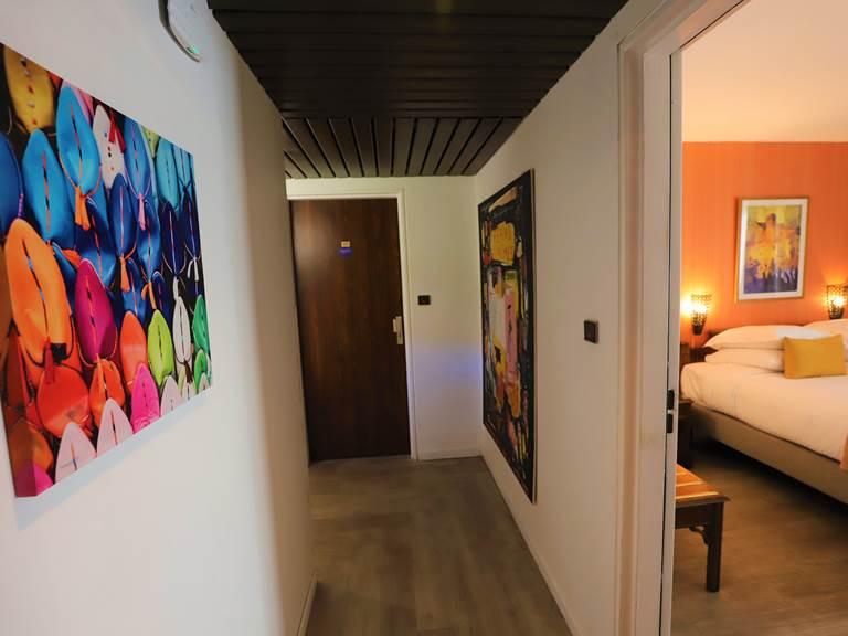Couloir avec tableaux et chambre triple petit balcon