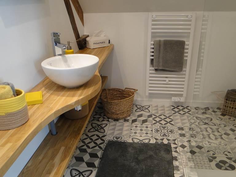 Salle de bain avec douche à l'italienne. Plan en chêne massif et sol en carreaux de ciment