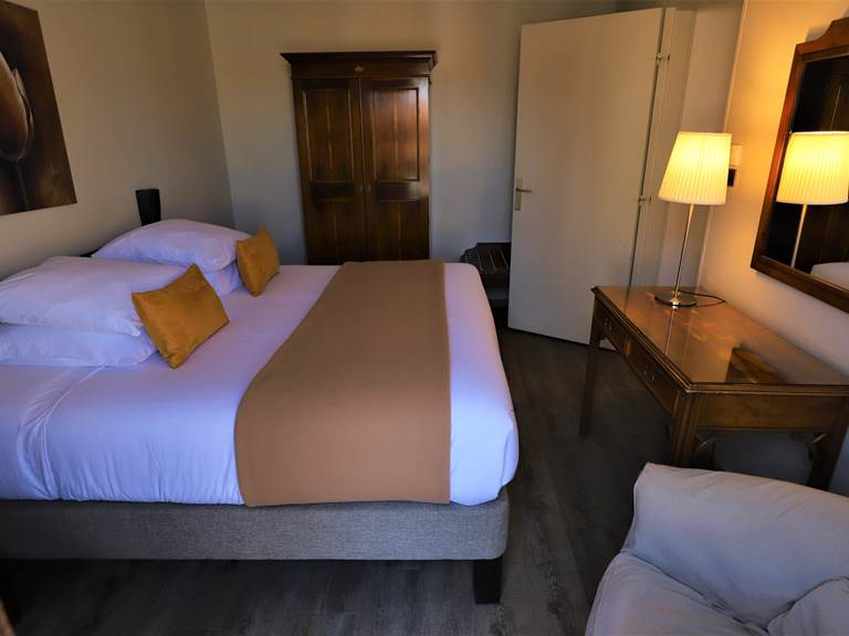 Chambre avec grand lit, fauteuil et armoire