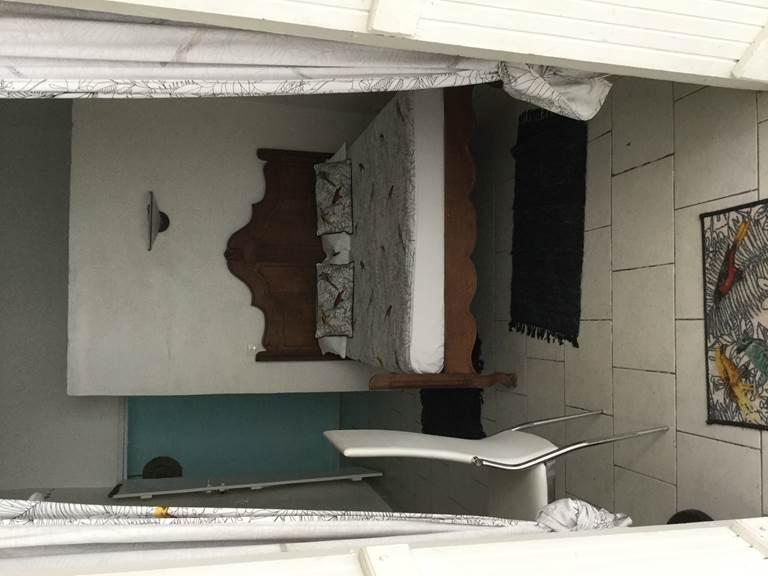 Notre plus petite chambre avec son lit baldequin, armoire, bureau, salle d'eau avec douche ,lave main et toilette, cuisine équipée sur terrasse, fresque d peint au fond sur brise vue.