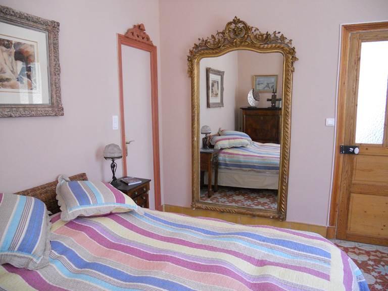 La décoration est typique de la période art déco  grand miroir, lustre art déco, armoire de même style, La porte de gauche donne dans la salle de bain.