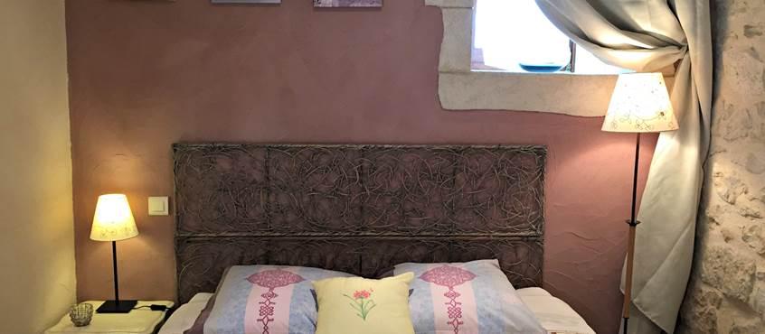 Chambre avec lit queen size, murs en pierre, peinture à la chaux
