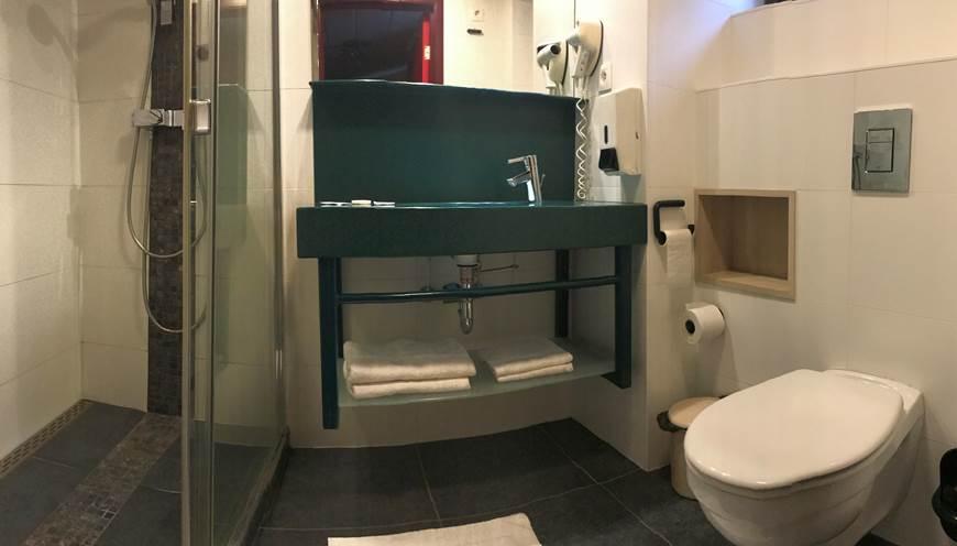 Salle de Bain privative comprenant une douche italienne, un lavabo, un sèche cheveux et toilettes. Savon, shampoing  douche, papier wc, serviettes de main et serviettes de bain.
