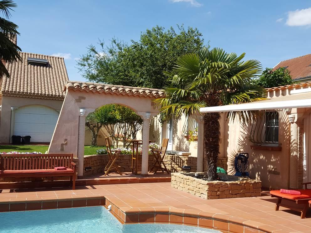 façade du pool house avec sa terrasse privative salon de jardin table et chaise mange debout